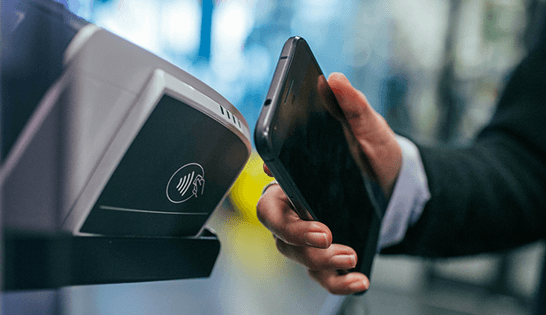 automation in banking: user holds cell phone near reader