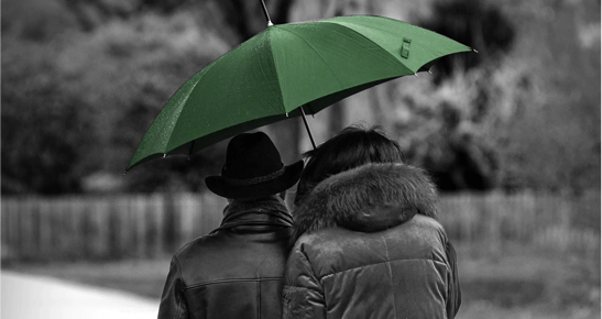 insurance automation: two people huddled under green umbrella