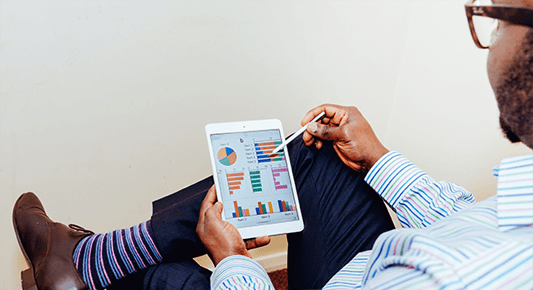 financial process automation: man looking at data charts on a tablet